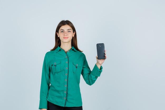 Jong meisje in groene blouse, zwarte broek die telefoon in één hand houdt en leuk, vooraanzicht kijkt.