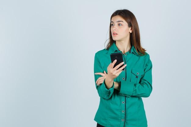 Jong meisje in groene blouse, zwarte broek die telefoon vasthoudt, wegkijkend en gericht, vooraanzicht kijkt.