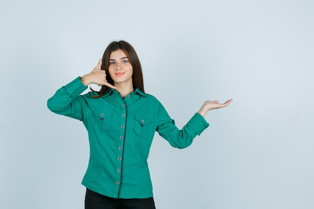 Jong meisje in groene blouse, zwarte broek die telefoongebaar toont, palm opzij spreidt en optimistisch, vooraanzicht kijkt.