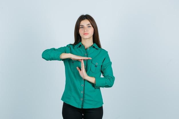 Jong meisje in groene blouse, zwarte broek die time-break gebaar toont en ernstig, vooraanzicht kijkt.
