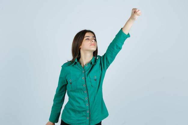 Jong meisje in groene blouse, zwarte broek die winnaargebaar toont en gelukkig, vooraanzicht kijkt.