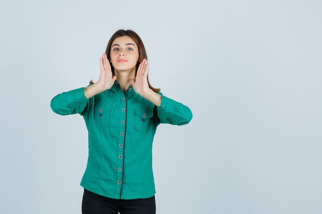 Jong meisje in groene blouse, zwarte broek hand in hand in de buurt van hoofd en op zoek schattig, vooraanzicht.