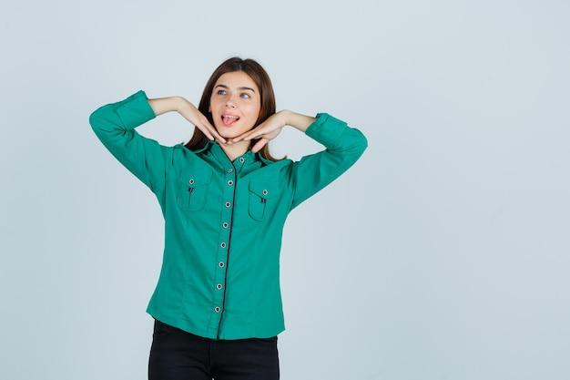Jong meisje in groene blouse, zwarte broek hand in hand onder de kin, mond wijd openhoudend en schattig, vooraanzicht op zoek.