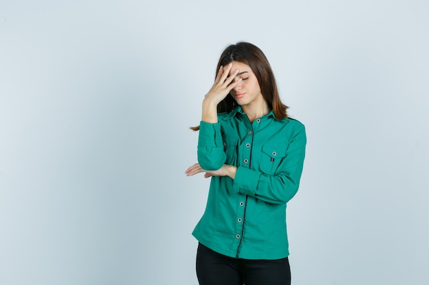 Jong meisje in groene blouse, zwarte broek hand op het voorhoofd te zetten en op zoek naar gekwelde, vooraanzicht.
