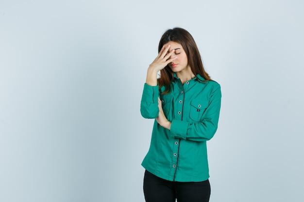 Jong meisje in groene blouse, zwarte broek hand op het voorhoofd te zetten en uitgeput, vooraanzicht op zoek.