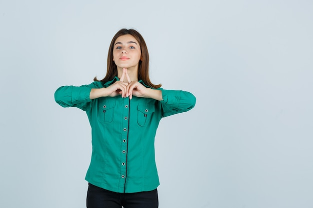 Jong meisje in groene blouse, zwarte broek houdt wijsvingers onder de kin en kijkt schattig, vooraanzicht.