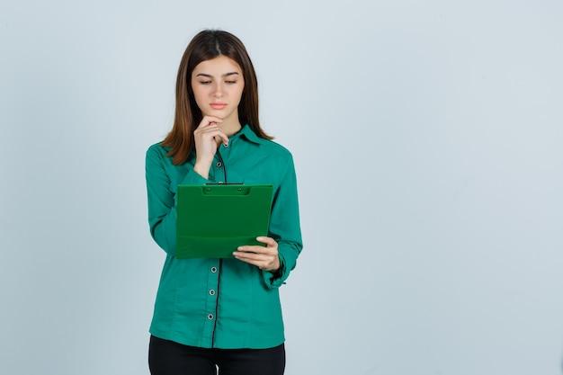 Jong meisje in groene blouse, zwarte broek kijken naar klembord, kin steunen en op zoek gericht, vooraanzicht.