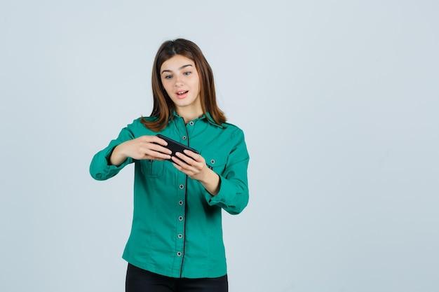 Jong meisje in groene blouse, zwarte broek kijken naar video's op telefoon en op zoek verrast, vooraanzicht.