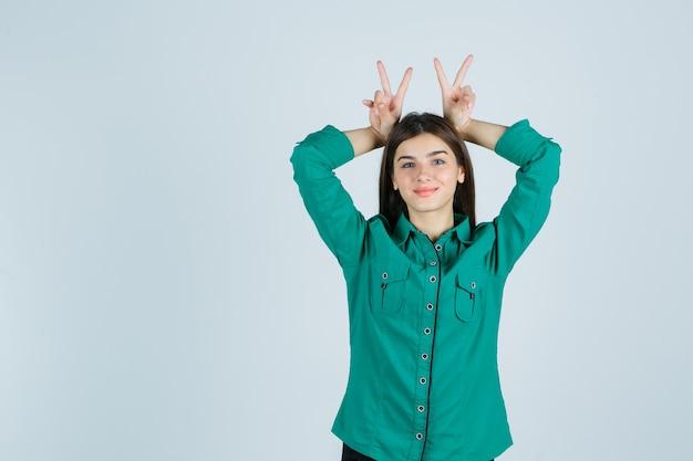 Jong meisje in groene blouse, zwarte broek maken konijnenoren boven het hoofd en ziet er schattig, vooraanzicht uit.