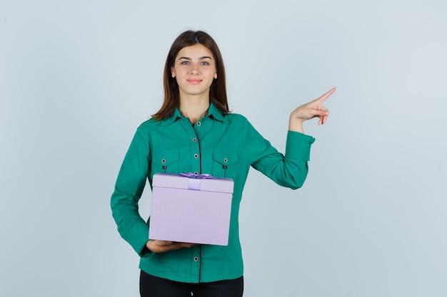 Jong meisje in groene blouse, zwarte broek met geschenkdoos, naar rechts wijzend met wijsvinger en op zoek gelukkig, vooraanzicht.