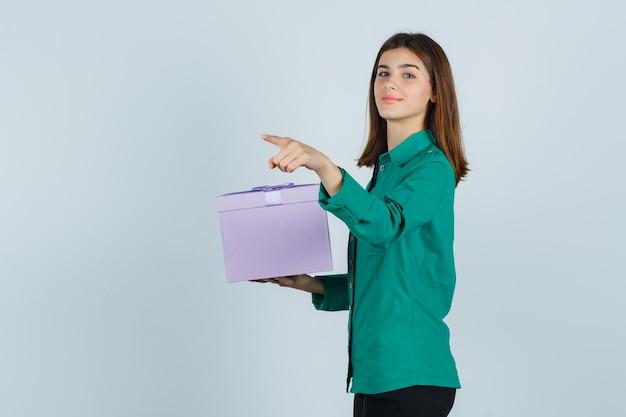 Jong meisje in groene blouse, zwarte broek met geschenkdoos, wegwijzend met wijsvinger en op zoek vrolijk, vooraanzicht.