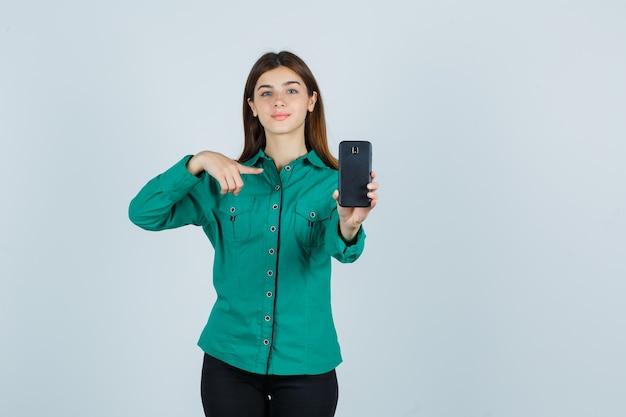 Jong meisje in groene blouse, zwarte broek met telefoon in de ene hand, erop wijzend met wijsvinger en op zoek vrolijk, vooraanzicht.