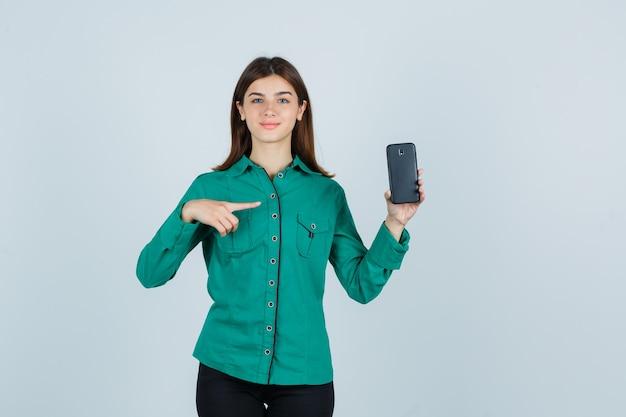 Jong meisje in groene blouse, zwarte broek met telefoon in de ene hand, erop wijzend met wijsvinger en ziet er schattig uit, vooraanzicht.