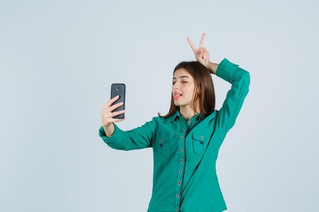 Jong meisje in groene blouse, zwarte broek met vredesgebaar boven het hoofd terwijl ze videogesprek voert en geamuseerd kijkt, vooraanzicht.