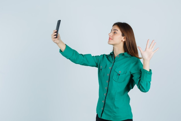 Jong meisje in groene blouse, zwarte broek selfie met telefoon te nemen, hand opsteken om hallo te zeggen en er vrolijk, vooraanzicht uit te zien.
