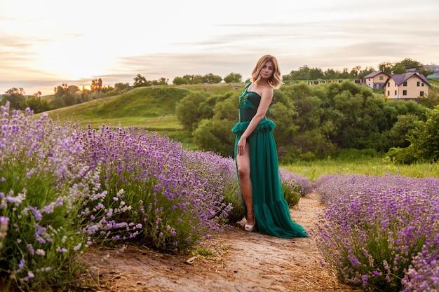 Jong meisje in groene jurk poseren op lavendelveld