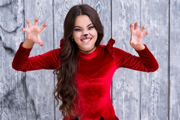 Jong meisje in halloween-kostuum het stellen