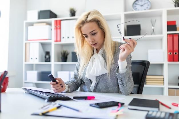 Jong meisje in het bureau dat met een teller en documenten werkt.