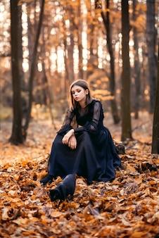 Jong meisje in het herfstbos zit op een boomstronk. een zwarte kat loopt in de buurt.