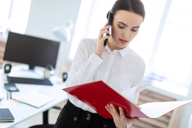 Jong meisje in het kantoor in de buurt van het rek en bladert door de map met de documenten en spreekt aan de telefoon.