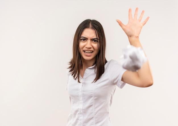 Jong meisje in het wit gooien verfrommeld stuk papier met geïrriteerde uitdrukking staande over witte muur