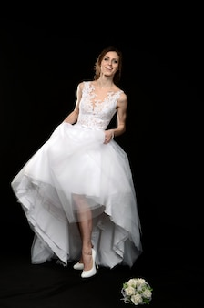 Jong meisje in het wit in een trouwjurk op blote voeten, emotionele gelukkig mysterieuze bruid op een zwarte achtergrond.