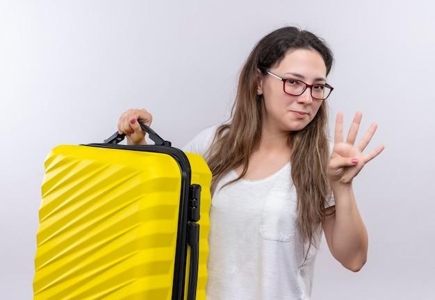 Jong meisje in het witte de reiskoffer van de t-shirtholding tonen en met vingers nummer drie het glimlachen benadrukken