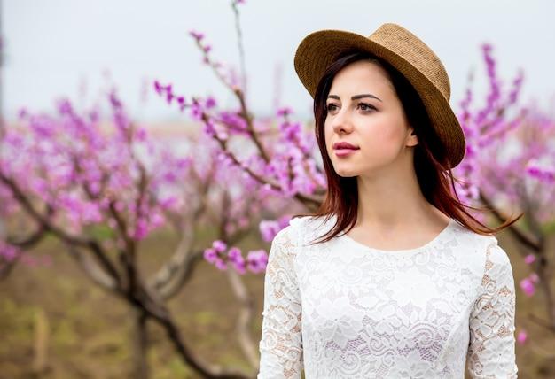Jong meisje in hoed dichtbij bloesemperzikboom