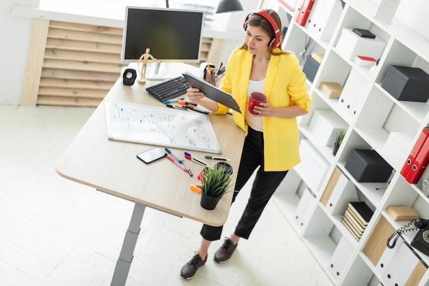 Jong meisje in hoofdtelefoons die met documenten werken en van een rode kop drinken