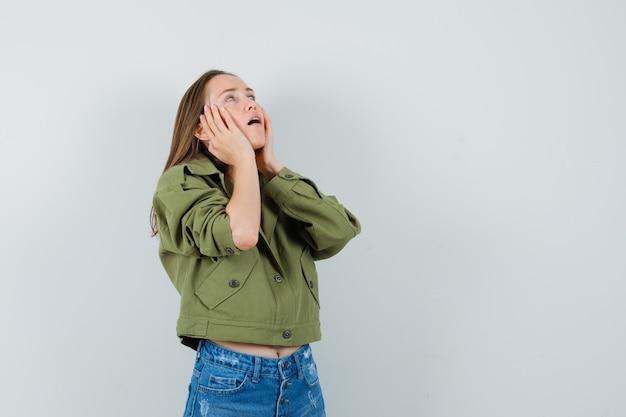Jong meisje in jas, korte broek, hand in hand op de wangen en op zoek moe, vooraanzicht.