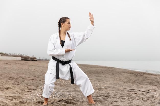 Jong meisje in karatekostuum het uitoefenen