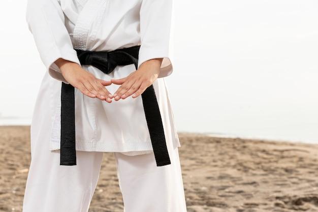 Jong meisje in karatekostuum openlucht