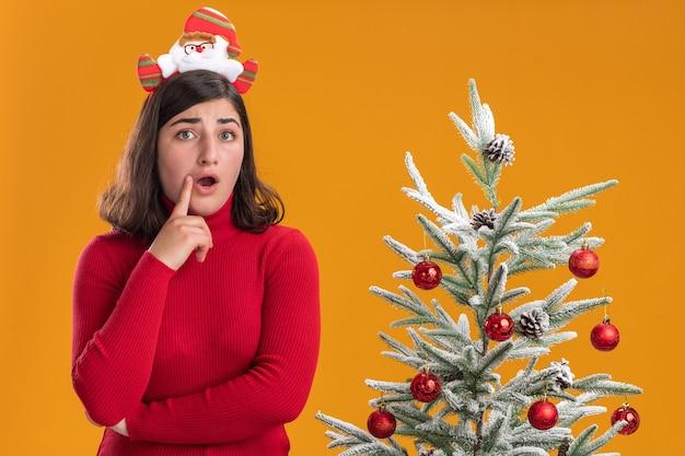 Jong meisje in kerst trui dragen grappige hoofdband kijken camera verrast staande naast een kerstboom over oranje achtergrond