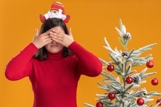 Jong meisje in kerstmissweater die grappige hoofdband draagt die ogen behandelt met handen naast een kerstboom over oranje achtergrond