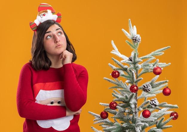 Jong meisje in kerstmissweater die grappige hoofdband draagt die verbaasd status naast een kerstboom over oranje muur kijkt