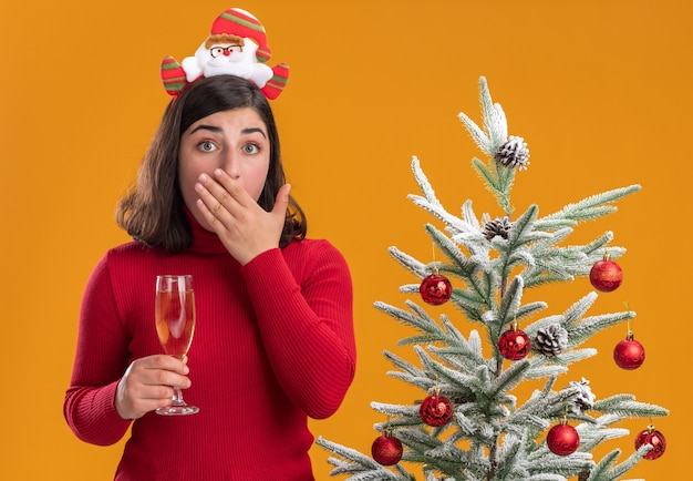 Jong meisje in kerstmissweater die grappige hoofdband draagt en glas champagne naast een kerstboom houdt over oranje achtergrond