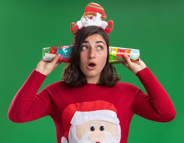 Jong meisje in kerstmissweater die santahoed draagt die kleurrijke document kopjes dichtbij haar oren houdt die opzij verrast status over groene muur kijken