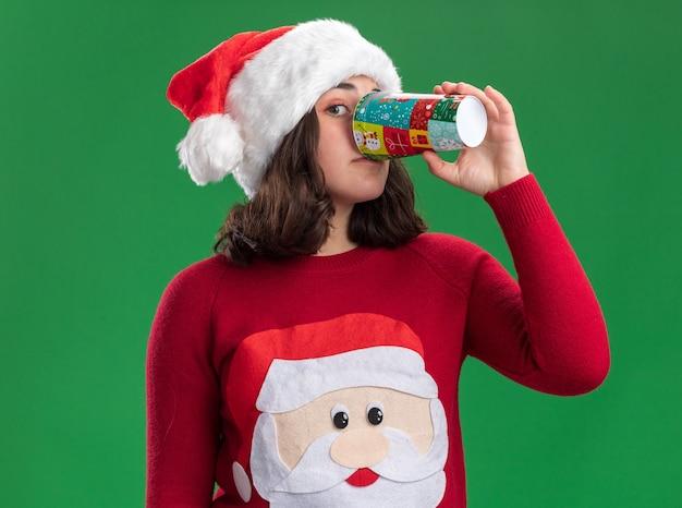 Jong meisje in kerstmissweater die santahoed dragen die uit kleurrijke document kop drinken die zich over groene muur bevinden
