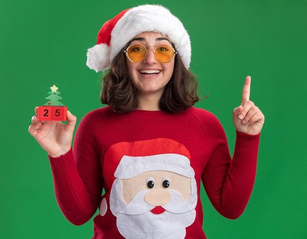 Jong meisje in kerstmissweater die santahoed en bril draagt die stuk speelgoed kubussen met nummer vijfentwintig houdt gelukkig en vrolijk toont wijsvinger die zich over groene muur bevindt