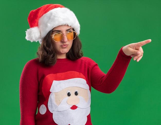 Jong meisje in kerstmissweater die santahoed en glazen dragen die opzij kijken ontevreden wijzend met wijsvinger op iets dat zich over groene muur bevindt