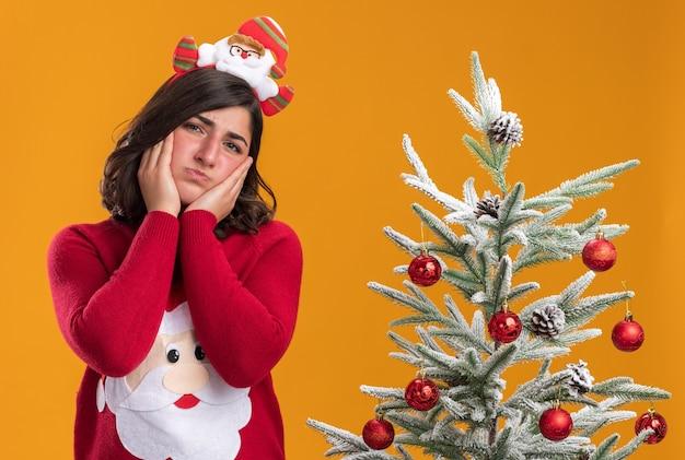 Jong meisje in kersttrui met grappige hoofdband die naar de camera kijkt met een droevige uitdrukking op het gezicht dat naast een kerstboom staat over oranje achtergrond
