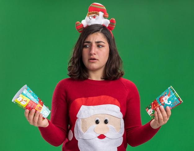 Jong meisje in kersttrui met kerstmuts die kleurrijke papieren bekertjes vasthoudt die ze verward bekijken terwijl ze proberen een keuze te maken met twijfels die over groene muur staan
