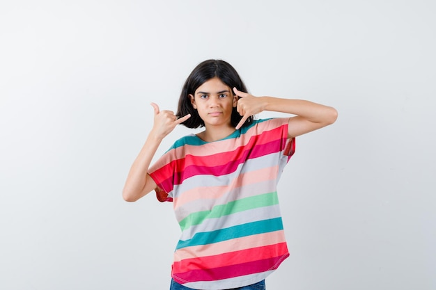 Jong meisje in kleurrijk gestreept t-shirt met bel me gebaren en zelfverzekerd, vooraanzicht.