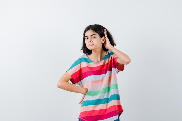 Jong meisje in kleurrijk gestreept t-shirt met een hand op de taille, een andere hand in de buurt van het oor om iets te horen en er gefocust uit te zien, vooraanzicht.