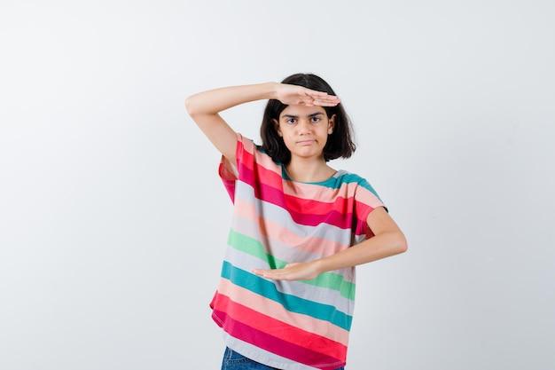Jong meisje in kleurrijk gestreept t-shirt met schubben en serieus, vooraanzicht.