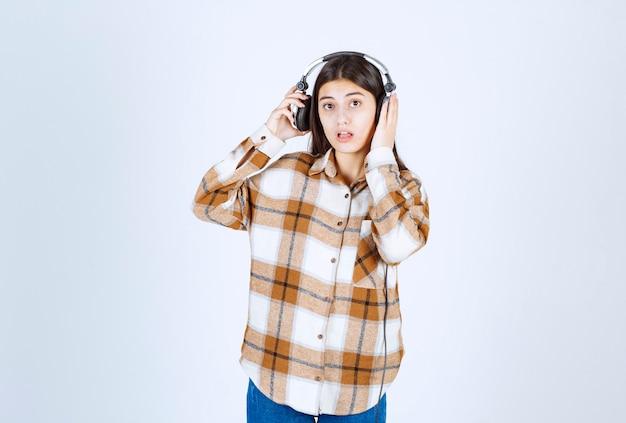 Jong meisje in koptelefoon poseren op witte muur.