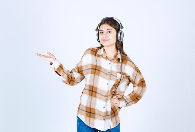 Jong meisje in koptelefoon staande op witte muur.