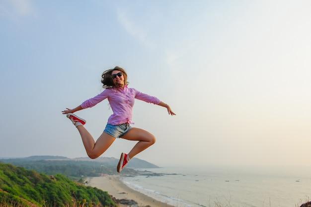 Jong meisje in korte broek en roze shirt springt zorgeloos op een heuvel tegen de zee. levensstijlbeeld van gelukkige reizigersvrouw. vrijheid en geluk concept. leven in beweging