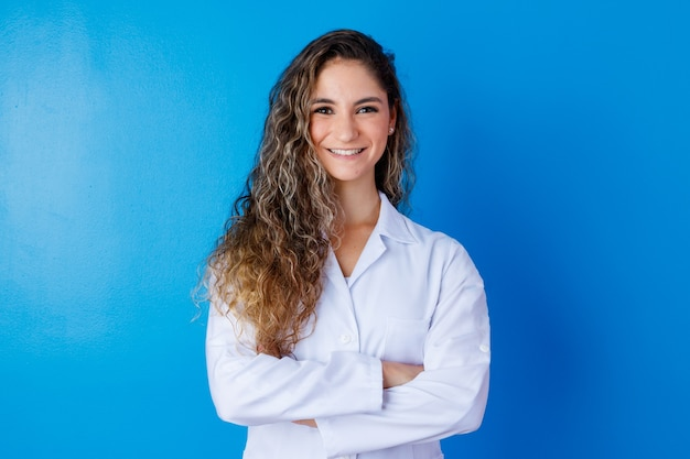 Jong meisje in laboratoriumjas op blauw met ruimte voor tekst