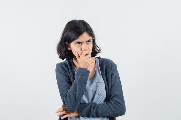 Jong meisje in lichtgrijs t-shirt en donkergrijze hoodie met rits aan de voorkant die mond bedekt met hand, staande in denkhouding en peinzend kijkend,